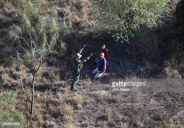 Border Patrol agent detains undocumented immigrants after capturing them in thick brush near the U.S.-Mexico border on December 10, 2015 at La...