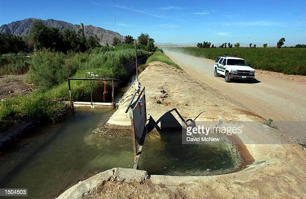 Border Patrol agent drives along an irrigation canal separating the U.S. From Mexico, at left, that carries Colorado River water from the All...