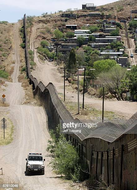 S Border Patrol agent drives along the steel wall separating the US from Mexico May 14 2006 in Nogales Arizona US President George W Bush will...