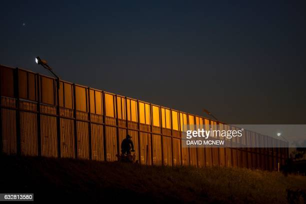 TOPSHOT A border patrol agent drives along the US Mexico border crossing on January 26 2017 in San Ysidro California President Donald Trump has...
