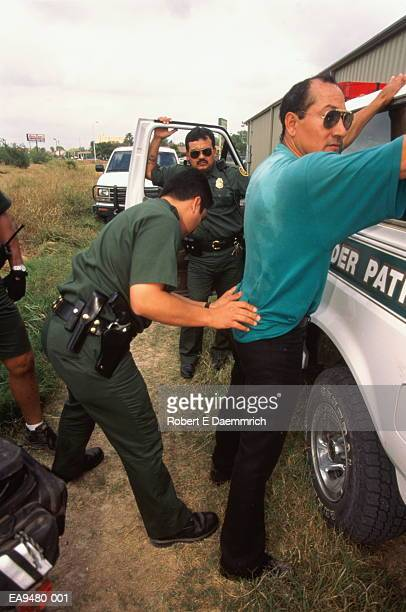 U.S. Border Patrol agent frisking caught illegal alien, Texas, USA