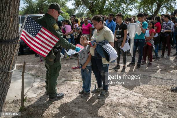 S Border Patrol agent gathers personal effects from immigrants before they were transferred to a McAllen processing center on July 02 2019 in Los...