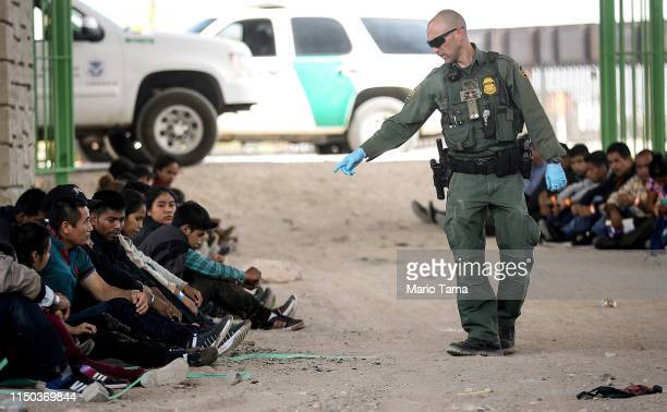 S Border Patrol agent gestures towards migrants being detained after crossing to the US side of the USMexico border barrier on May 19 2019 in El Paso...