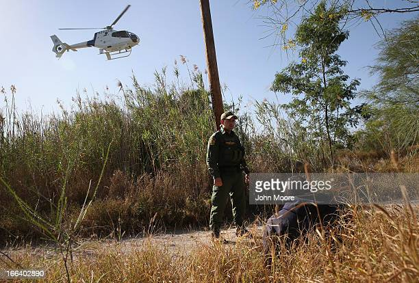 S Border Patrol agent guards a suspected drug smuggler on April 11 2013 in Mission Texas Border Patrol agents with helicopter support from the Office...