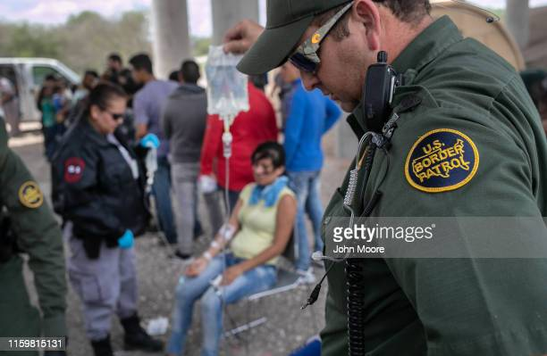 Border Patrol agent holds an IV bag for an immigrant suffering from heat exhaustion after taking her into custody on July 02, 2019 in McAllen, Texas....