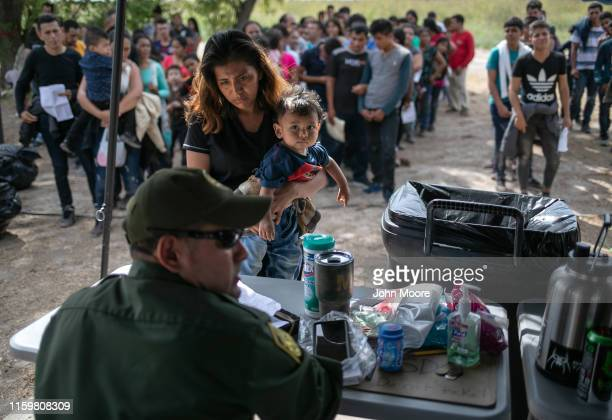 S Border Patrol agent interviews immigrants after taking them into custody on July 02 2019 in Los Ebanos Texas Hundreds of immigrants most from...