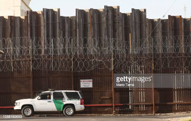 Border Patrol agent is posted in front of the U.S.-Mexico border barrier in Imperial County, which has been hard-hit by the COVID-19 pandemic, on...