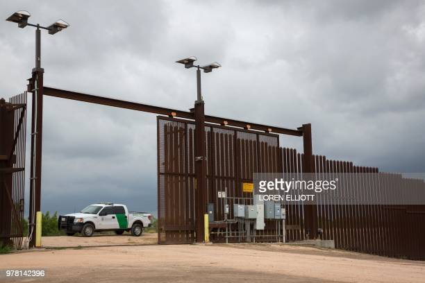 Border Patrol agent keeps watch at a gate On the USMexico border fence on June 18 2018 near San Benito Texas President Donald Trump vowed on June 18...