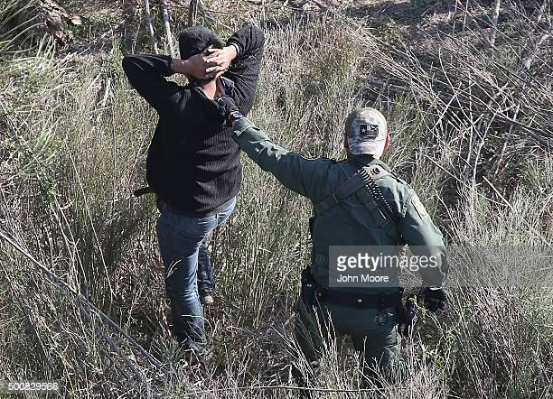 Border Patrol agent leads an undocumented immigrant out the brush after capturing him near the U.S.-Mexico border on December 10, 2015 at La Grulla,...