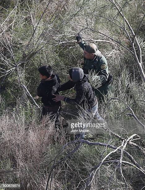 Border Patrol agent leads juvenile undocumented immigrants out of thick brush after capturing them near the U.S.-Mexico border on December 10, 2015...