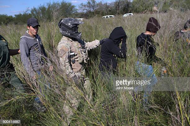S Border Patrol agent leads undocumented immigrants after capturing them near the USMexico border on December 7 2015 near Rio Grande City Texas...