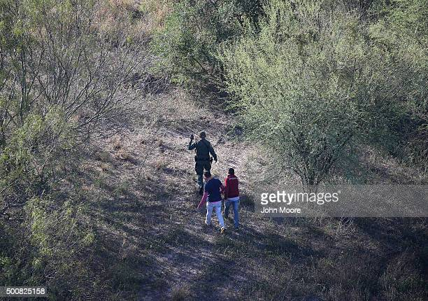 Border Patrol agent leads undocumented immigrants out of thick brush after capturing them near the U.S.-Mexico border on December 10, 2015 at La...