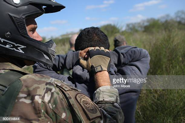 Border Patrol agent leads undocumented immigrants through the brush after capturing them near the U.S.-Mexico border on December 7, 2015 near Rio...