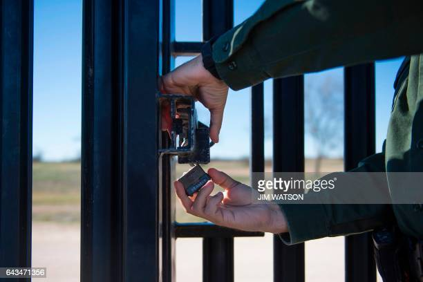 Border Patrol agent locks a gate on the border fence at the US/Mexico border in Del Rio Texas on February 21 2017 this image is part of an ongoing...