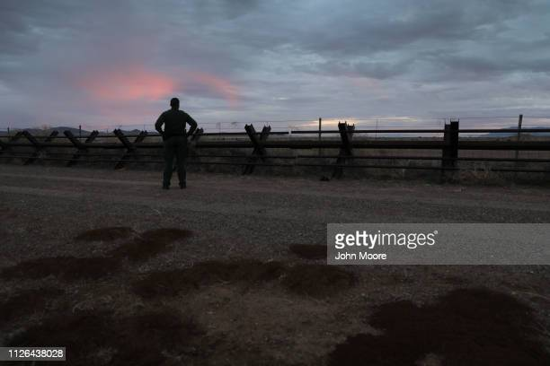 S Border Patrol agent looks over the Normandystyle border fence at the USMexico border at sunset on January 30 2019 in Antelope Wells New Mexico...