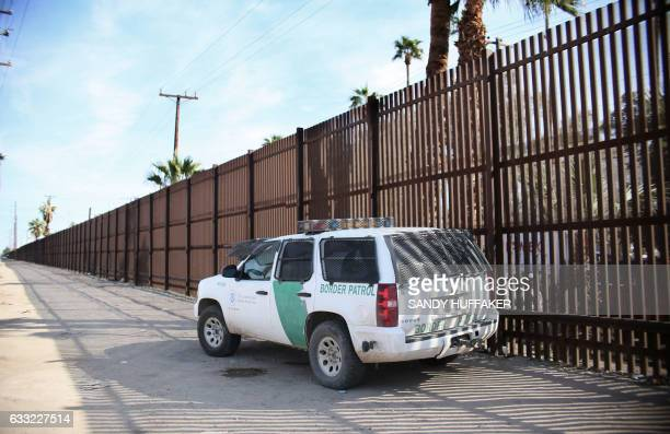 A Border Patrol agent looks over the USMexico border wall in Calexico California in the Imperial Valley on Tuesday January 31 2017 Many of the farm...
