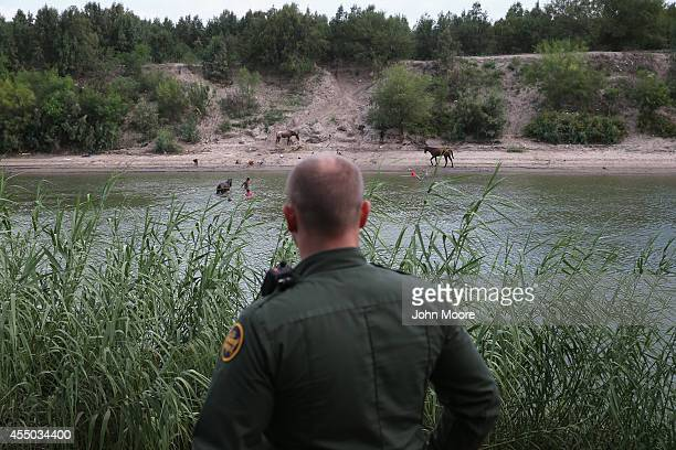 S Border Patrol agent looks towards Mexico from the bank of the Rio Grande River on September 8 2014 near McAllen Texas Although the numbers of...