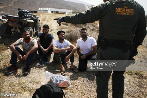 Border Patrol agent monitors a group of apprehended males from India who illegally crossed the U.S.-Mexico border on July 16, 2018 in San Diego,...