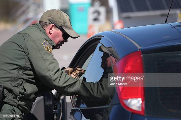 S Border Patrol agent prepares to search a car entering the United States from Mexico on February 26 2013 in Nogales Arizona Some 15000 people cross...