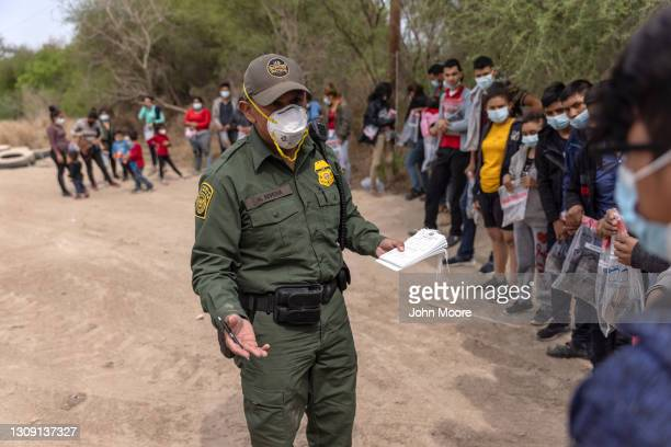 Border Patrol agent questions an unaccompanied minor after a group of asylum seekers crossed the-Rio Grande into Texas on March 25, 2021 in Hidalgo,...