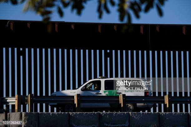 Border Patrol agent sits in a vehicle along a border wall near the US Customs and Border Protection San Ysidro Port of Entry at the US Mexico border...