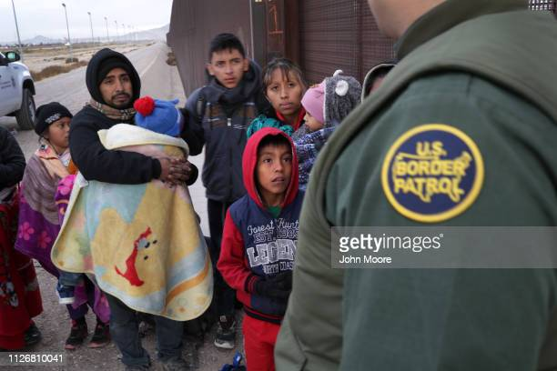S Border Patrol agent speaks with Central American immigrants at the USMexico border fence on February 01 2019 in El Paso Texas The migrants were...