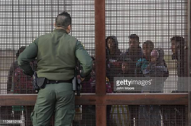 S Border Patrol agent speaks with Central American immigrants at the border fence after they crossed the Rio Grande from Mexico on February 01 2019...