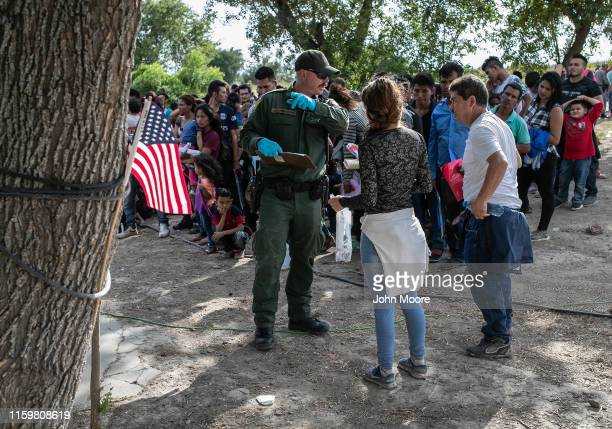 S Border Patrol agent speaks with immigrants before they were transferred to the McAllen Border Patrol facility on July 02 2019 in Los Ebanos Texas...