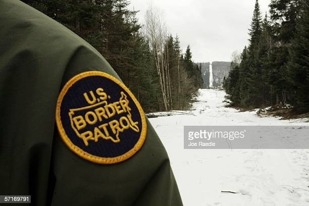S Border Patrol agent stands along the boundary marker cut into the forest marking the line between Canadian territory on the right and the United...
