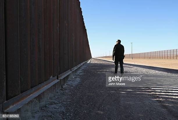 S Border Patrol agent stands at the USMexico border fence on November 17 2016 in San Luis Arizona The US government has built triple fencing to deter...