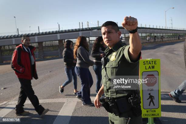 S Border Patrol agent stops traffic as immigrants are deported across an international bridge into Mexico on March 14 2017 from Hidalgo Texas The...