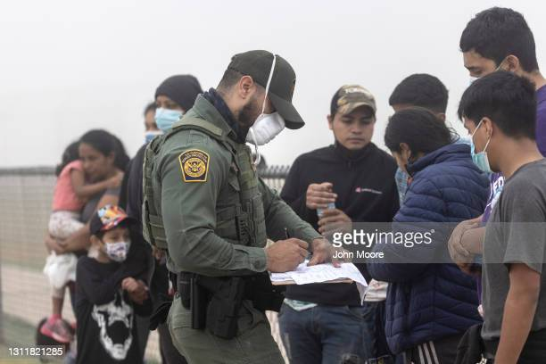 Border Patrol agent takes the names of Central American immigrants near the U.S.-Mexico border on April 10, 2021 in La Joya, Texas. A surge of...