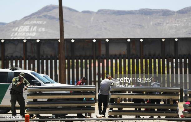 Border Patrol agent uses his radio as detained migrants wait after crossing to the U.S. Side of the U.S.-Mexico border barrier on May 18, 2019 in El...