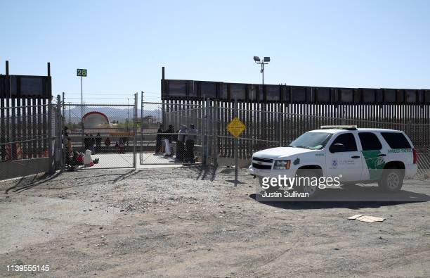 Border Patrol agent vehicle sits next to detained migrants as they wait to be transported at the border of the United States and Mexico on March 31,...