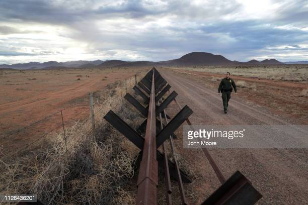 Border Patrol agent walks along the U.S.-Mexico border fence on January 30, 2019 in Antelope Wells, New Mexico. Since October, dozens of large groups...