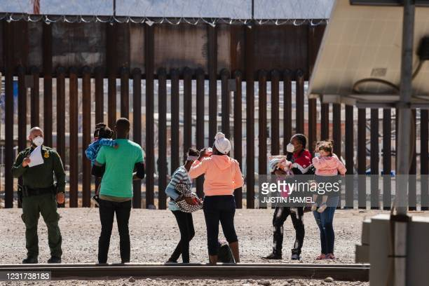 Border Patrol agents apprehend a group of migrants near downtown El Paso, Texas following the congressional border delegation visit on March 15,...