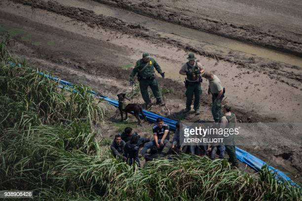 Border Patrol agents apprehend illegal immigrants near the US border with Mexico on March 27 2018 in the Rio Grande Valley Sector near McAllen Texas