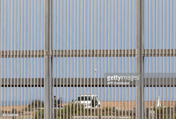 Border Patrol agents are seen through the border fence detaining a person at the Border Field Park in Playas de Tijuana in Tijuana northwestern...
