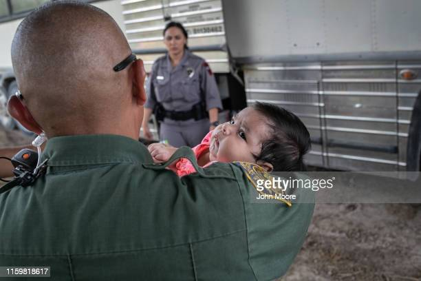 Border Patrol agents briefly holds an infant after she and her mother were taken into custody by U.S. Border Patrol agents on July 02, 2019 in...