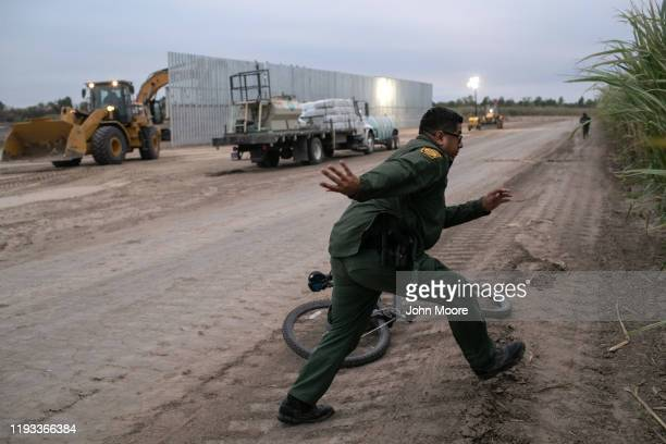 S Border Patrol agents chases a group of undocumented immigrants near a section of privatelybuilt border wall under construction on December 11 2019...