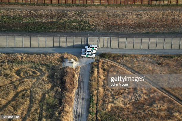 S Border Patrol agents confer next to the USMexico border fence as seen from a helicopter on May 11 2017 in San Diego California The border spans...
