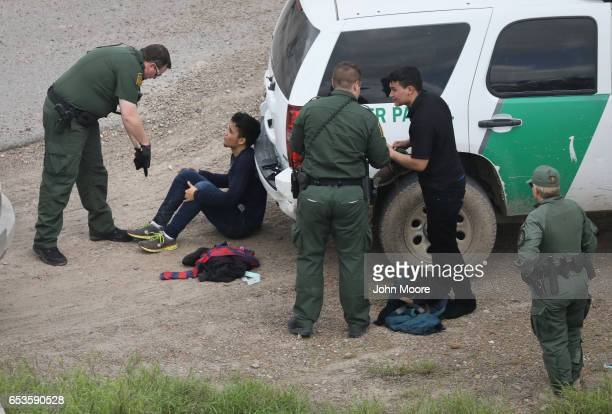S Border Patrol agents detain two undocumented immigrants after capturing them near the USMexico border on March 15 2017 near McAllen Texas US...