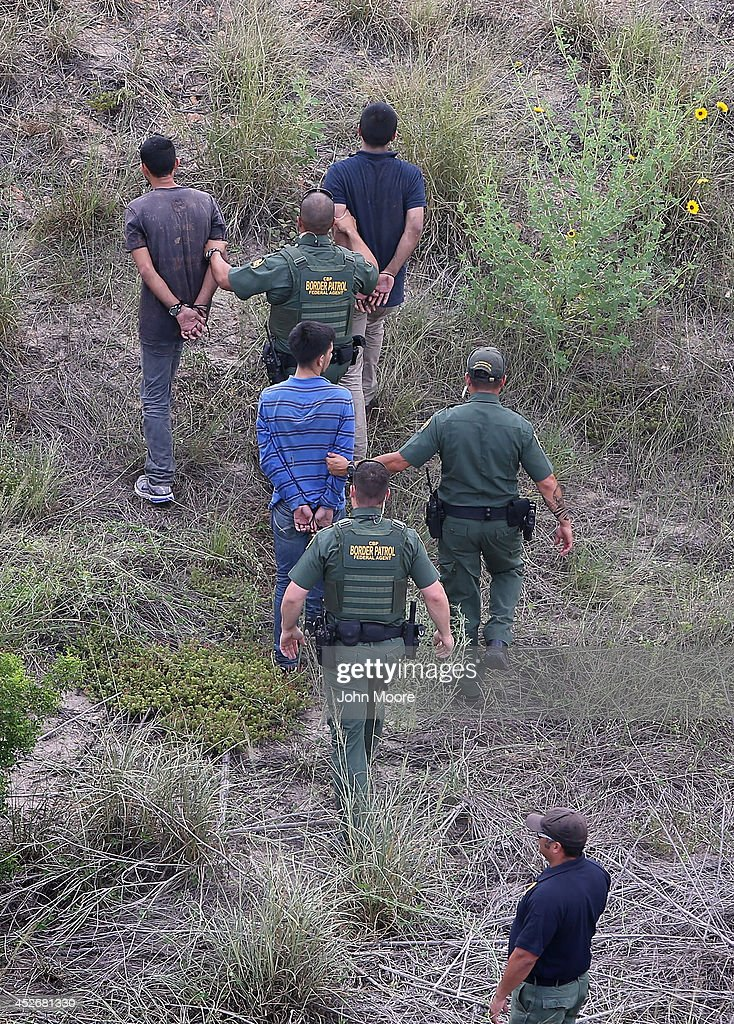 U.S. Border Patrol agents detain undocumented immigrants after a foot chase on July 25, 2014 near Falfurrias, Texas. Tens of thousands of illegal immigrants have crossed into the U.S. this year, causing a humanitarian crisis on the U.S.-Mexico border. Texas' Rio Grande Valley has become the epicenter of the latest immigrant crisis, as more Central Americans have crossed illegally from Mexico into that sector than any other stretch of America's 1,933 mile border with Mexico.