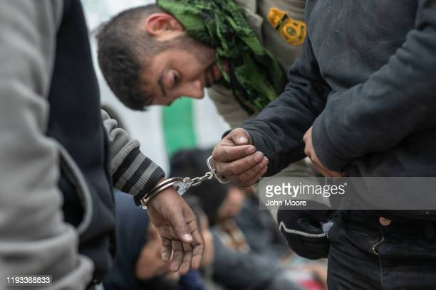 Border Patrol agents detain undocumented immigrants at a construction site for a privately-built border wall on December 11, 2019 near Mission,...