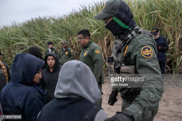 Border Patrol agents detain undocumented immigrants caught near a section of privately-built border wall under construction on December 11, 2019 near...