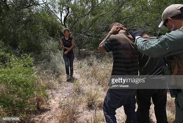 S Border Patrol agents detain undocumented immigrants in dense brushland some 60 miles north of the US Mexico border in Brooks County on July 23 2014...
