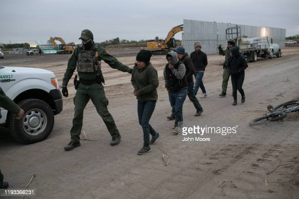Border Patrol agents detain undocumented immigrants near a section of privately-built border wall under construction on December 11, 2019 near...