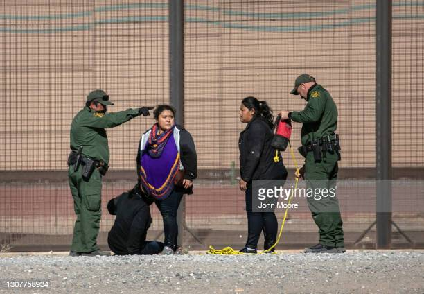 Border Patrol agents detain undocumented immigrants next to the U.S.-Mexico border fence after the women crossed the Rio Grande into El Paso on March...