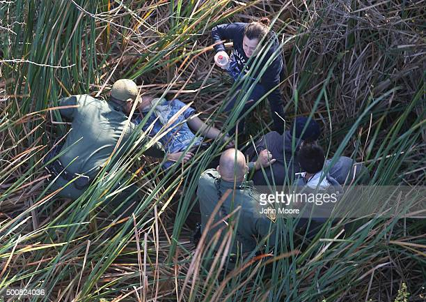 Border Patrol agents detain undocumented immigrants, one of them who needed medical attention, after capturing them in thick brush near the...