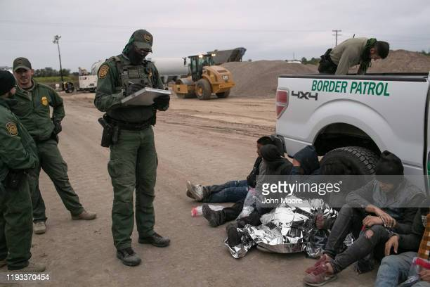 Border Patrol agents detain undocumented immigrants who they caught near the construction site of a privately-built border wall on December 11, 2019...